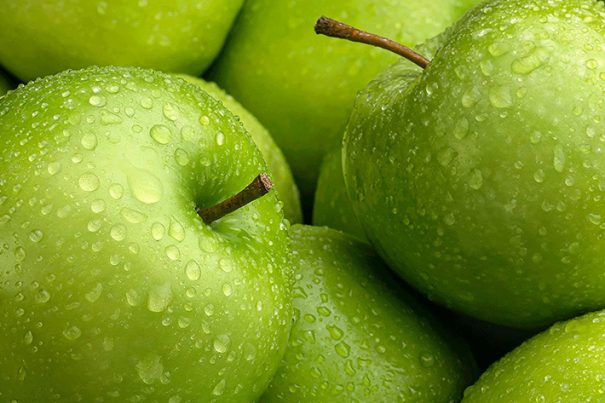 Close up of crisp green apples with water droplets on skin