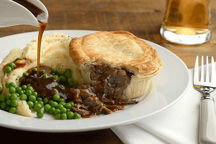 Gravy pouring onto plate of pie and mash