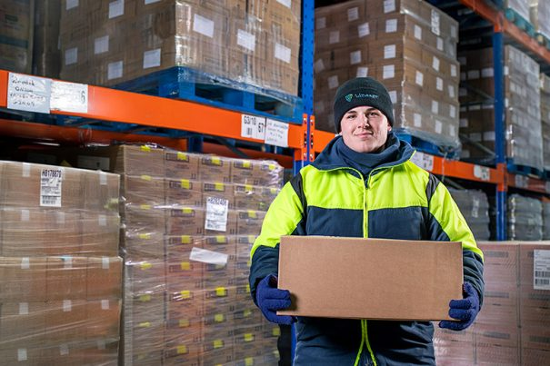 Coldstore worker in front of shelving holding a box